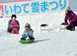 いわて雪まつりが開幕し、滑り台でそりを楽しむ来場者=7日、雫石町・岩手高原スノーパーク