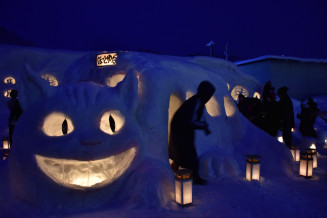 雪あかり2019inにしわがの様子。ネコバスの雪像に明かりがともされたJRほっとゆだ駅前の会場=2019年2月