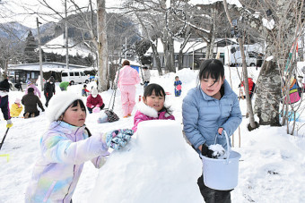 協力しながら雪だるまを作る参加者