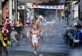 冷水を浴びて商店街を全力で駆け抜ける参加者=11日、一関市大東町大原