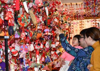 華やかなつるし雛飾りを鑑賞する家族連れ
