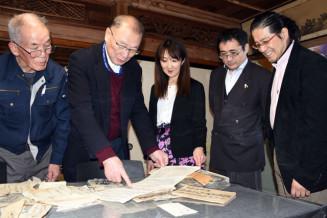 見つかった文書を読み解く「南部藩・復活酒プロジェクト」の布施かおり代表(中央)ら