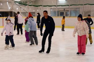 児童とスケートで交流を育むエバン・ライサチェクさん(中央)