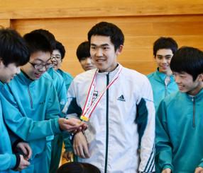 優勝のメダルを生徒に見せる鈴木塁人さん