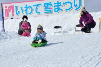滑り台でそりを楽しむいわて雪まつりの来場者=7日、雫石町・岩手高原スノーパーク