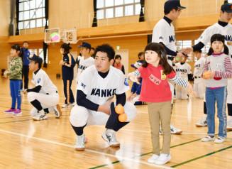 野球部員のアドバイスを受けながら、的を狙ってボールを投げる児童