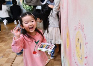 思い思いに園舎の壁にメッセージなどを書く子どもたち