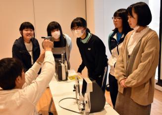 三好大輔さん(左)から8ミリフィルムの仕組みなどの指導を受ける大船渡高生