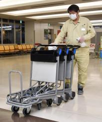 手荷物用カートを消毒する県空港ターミナルビルの従業員。花巻空港では国際定期便全2路線が休止となる=27日、花巻市