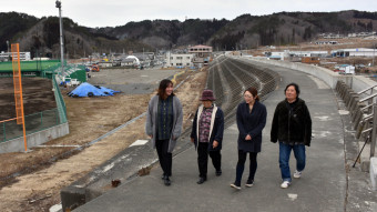 【2020年2月14日】 横浜市から移住し、地域を盛り上げる山本千香さん(左)。防潮堤左にある野球場や道の駅は台風豪雨で被災した