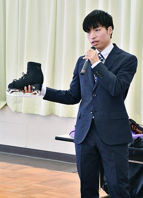 スケート靴を披露しながら、フィギュアスケートの楽しさについて語る佐藤洸彬さん