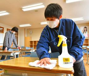 試験会場となる教室で、受験生が使う机を入念に消毒する関係者=5日、盛岡市本宮・盛岡商高
