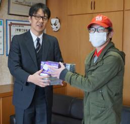 盛島徹校長(左)にマスクを手渡す岩崎竜也取締役(上野中提供)