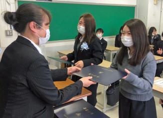 佐藤佳子副校長(左)から卒業証書を受ける学生