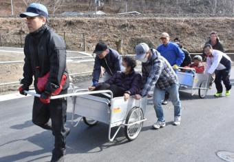 要援護者をリヤカーに乗せ、避難訓練を行う安渡地区の住民。15分ルールを設定し、迅速な避難意識を確認し合っている=2019年3月、大槌町安渡