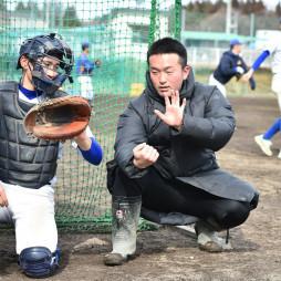 選手に捕球を指導する前川剛大コーチ(右)=盛岡市・盛岡大付高グラウンド