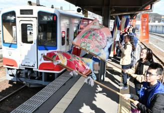 大漁旗を振って久慈駅に到着した列車を迎える地元住民ら=14日、久慈市中央