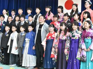 笑顔で記念撮影するTOSHI―LOWさん(前列中央)と卒業生。サプライズ出演し、36人の門出を祝った