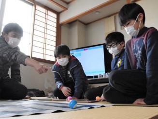 吉田力さん(左)に教わり、球状ロボットの操作を体験する子どもたち