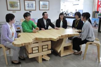 雫石町役場に設置された町産材のユニークなテーブル。和山忠吉さん(左から2人目)が制作した