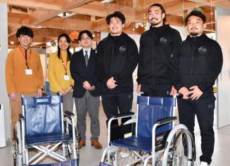 車いすを寄贈した釜石シーウェイブス(SW)RFCの(右から)小野航大選手、山田龍之介選手、中野裕太選手とかまいしDMCの関係者