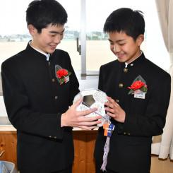 紙製のサッカーボールに書かれた寄せ書きを見つめる卒業生
