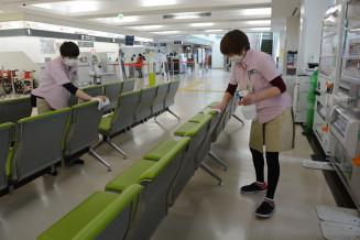 感染者の男性が利用したとみられる花巻空港のターミナルビル内で、消毒に当たる関係者=26日、花巻市