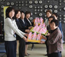 手作りの「おっほ人形」を町職員に贈呈するおっほ小学校の会員(右)