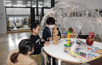 小田島組の本社で遊ぶ子どもたち。ガラス張りの奥では親たちが働いている=北上市藤沢