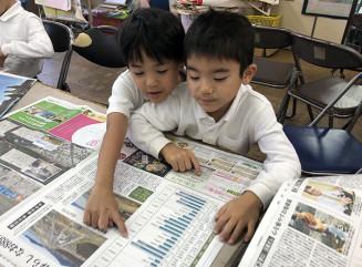 岩手日報の東日本大震災特別号外の記事を読みながら、感想を話し合う沖縄・大山小1年の大城京君(左)と仲村冬音君