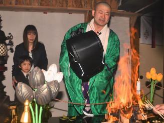 ランドセルを火に近づけ健康や交通安全を祈願する司東隆光副住職