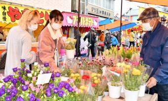 色とりどりの花の苗木を品定めする女性ら