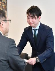 山本正徳市長から辞令書を受け取る吉浜知輝さん(右)