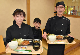食堂を開店する菅野勝さん(右)と妻美智代さん(左)。中央は長男尊斗(みこと)君