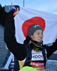 日本男子初の個人総合優勝を決め、日の丸を両手に掲げる小林陵侑選手(土屋ホーム)=10日、ノルウェー・オスロ