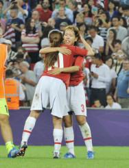 決勝で米国に敗れた日本。沢穂希さんと抱き合い、涙をこらえる岩清水梓さん(右)=2012年8月9日、英・ウェンブリー競技場