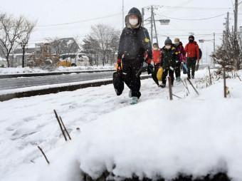 季節外れの雪空の下、マスク姿で登校する安代小の児童=6日、八幡平市清水