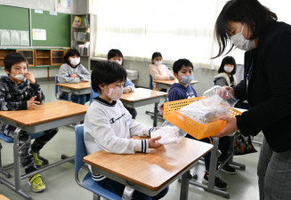 善意が込められた布マスクを受け取る普代小の4年生