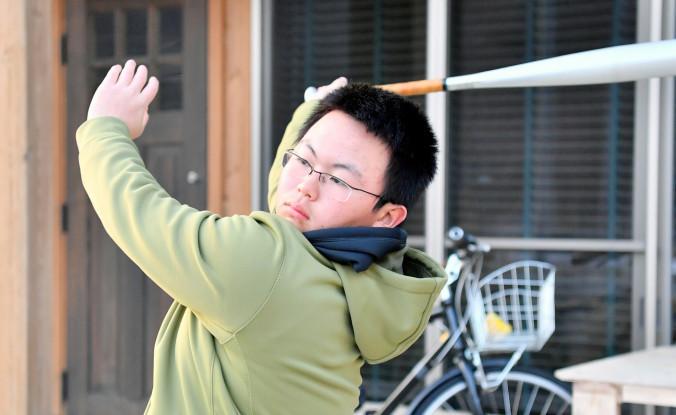 自らプロ野球選手を目指す夢を描き、自宅前で素振りをする古川真愛さん=11日、釜石市栗林町