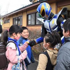 ハチマンタイラーから黄色い羽根を受け取り、交通安全を誓う松野小児童