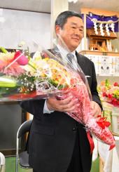 初当選し、花束を手にする晴山裕康氏=12日午後8時56分、九戸村伊保内の事務所