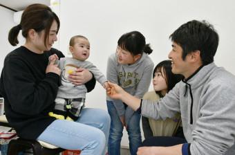 普代村の金子太一さん(右)一家。母佳子さん(左)に抱かれた颯天ちゃんを、姉の葵さん(左から3人目)、咲菜さん(同4人目)も温かく見守る=同村上村