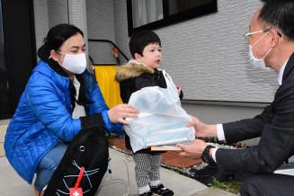 市職員からマスクを受け取る(左から)阿部優依さんと唯希ちゃん