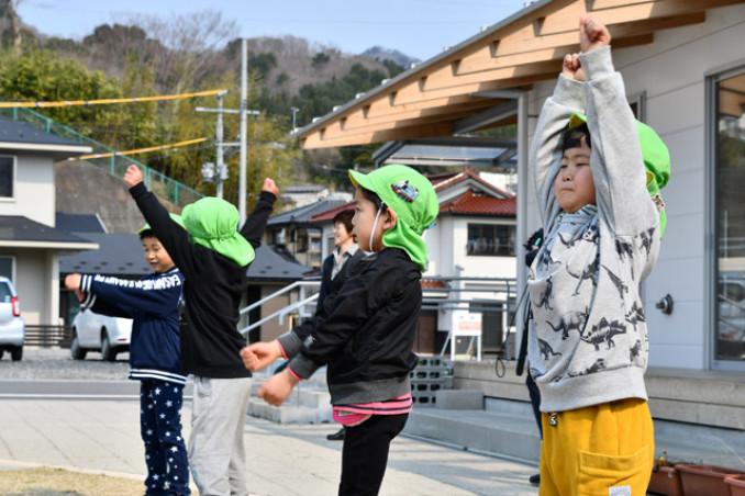青空の下、町に響き渡る放送に合わせて体を動かす園児たち