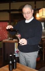 試作品の地コーラをコップに注ぐ佐藤航社長