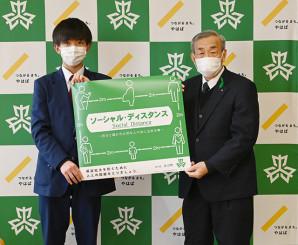 新型コロナウイルス感染症予防を啓発するポスターを掲げる小野寺悠来さん(左)と高橋昌造町長