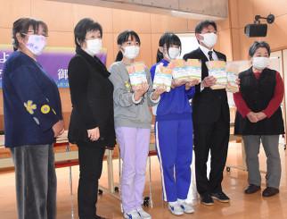 廃棄浴衣を使った手作りマスクを手にする御所小の児童ら