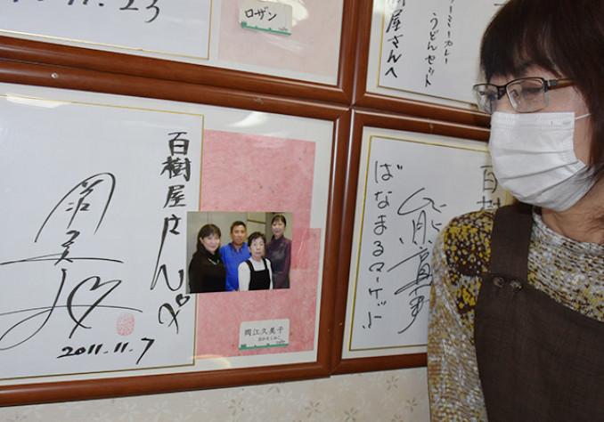岡江久美子さんから贈られたサインを見て哀悼の念を強くする今野由紀子店主=24日、大船渡市盛町