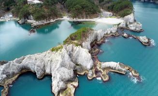 海上から望む浄土ケ浜。コバルトブルーに白岩が映える=宮古市日立浜町(本社小型無人機から撮影)