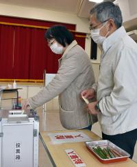 投票する有権者。使用した鉛筆はトレー(右手前)で回収して消毒を行い感染防止を図った=26日、大船渡市盛町